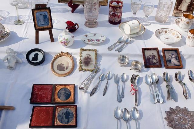 Photo d'un stand exposé au marché antiquités brocante de Lavaur : couverts, cadres, verres et vaisselle anciens sont exposés.