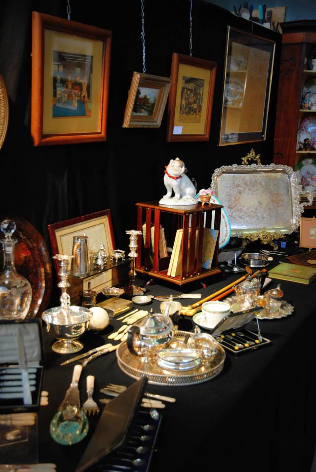 Détail d'un stand présentant des objets et de la vaisselle ancienne au salon des Antiquaires 2019.