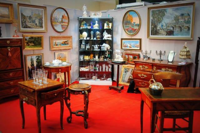 Stand d'un exposant présentant des meubles, tableaux et de la vaisselles ancienne au salon des Antiquaires 2019.