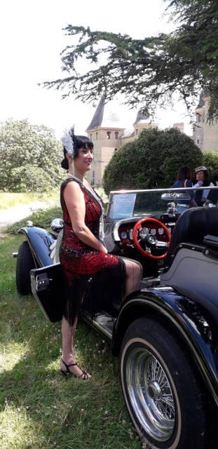 Valérie habillée à la mode des années 40 à côté de sa sublime voiture, une Excalibur.